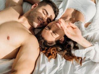 Top view of happy, couple smiling with closed eyes while lying in bed together