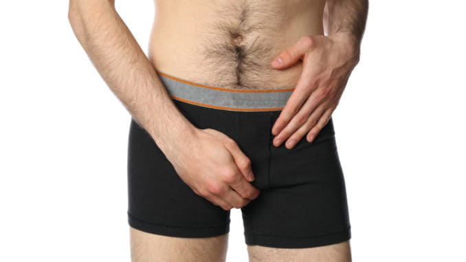 Man holding his groin, isolated on background. Men`s health