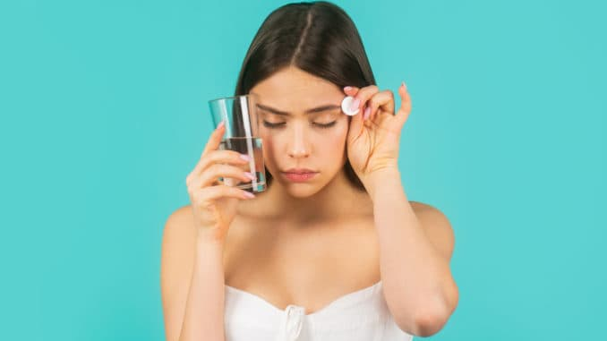 Young woman taking pill against headache. Brunette taking a pill with a glass of water. Woman taking drugs to releave