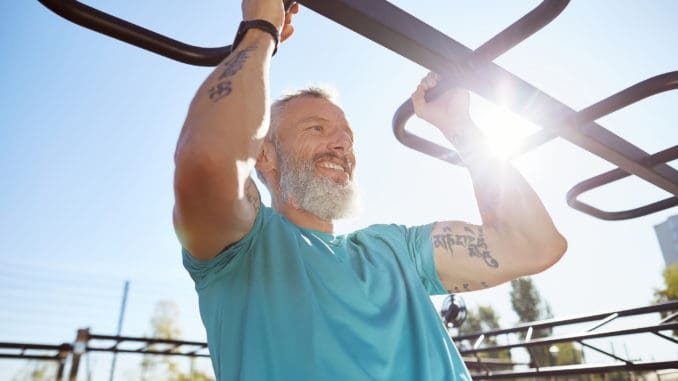 Strong and healthy people. Happy bearded senior man pulling up on horizontal bar and smiling while training outdoors. He is working out at the stadium. Fitness, sport, workout, healthy lifestyle