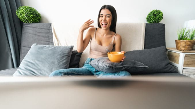 Happy woman eating cereal cup with milk while watching on computer laptop sitting on sofa - Health meal and living room entertainment concept