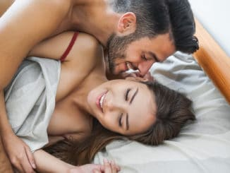 Happy couple having fun on bed under blanket -