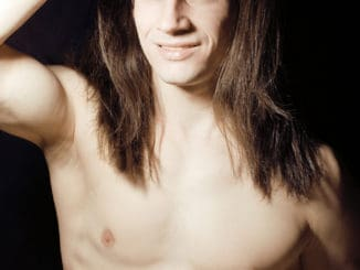 Handsome young man with long hair naked torso on black background smiling