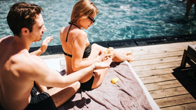 Young hot couple resting at swimpool.