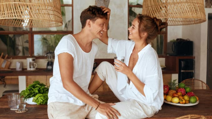 Healthy Diet. Couple Drinking Pure Water. Romantic Man Hugs Woman Touching His Hair And Holding Glass At Kitchen In Tropical Villa. Detox And Hydrate On Summer Vacation.