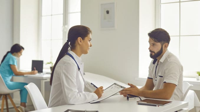 Medical clinic offfice. Young smiling woman doctor in medical uniform sitting and listening to talking man patient during consultation. Visiting doctor in hospital concept