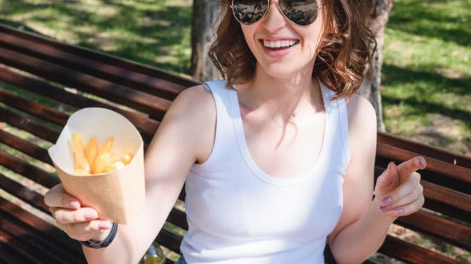 Beautiful, young woman eating fries in the street. The concept of fast food, food delivery and lunch in nature.