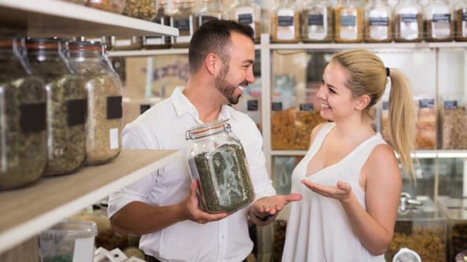 Happy women and men holding glass can with dried herbs in organic shop