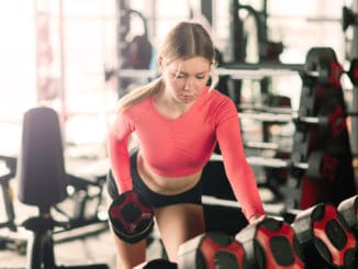 Young woman lifting weights at gym, training with dumbbells