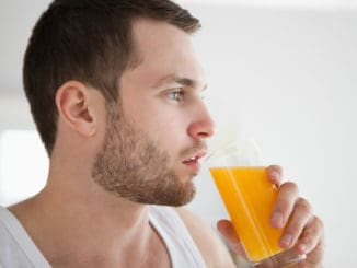 Close up of a healthy man drinking orange juice in his kitchen