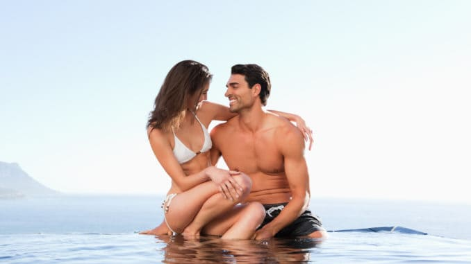 Couple sitting on the pool edge together