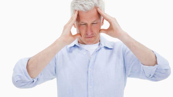 Tired man having a headache against a white background