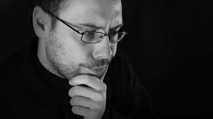 Man thinking with beard and glasses, white and black picture