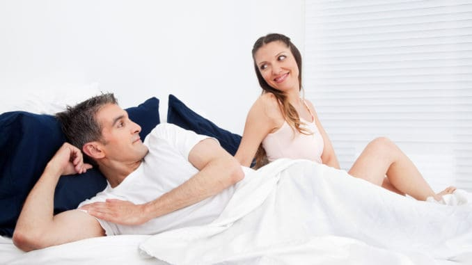 Happy smiling senior couple laying in bed