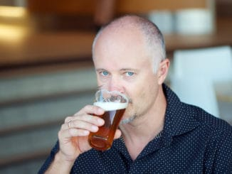 Middle aged man drinking beer from a glass in a pub, a bar or a restaurant