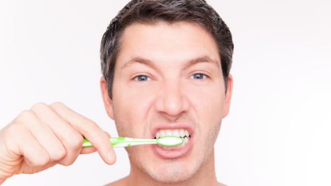 Teeth brushing man looking in mirror