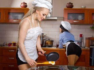 Beautiful young women frying eggs in kitchen