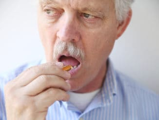 Front view of man taking a dietary supplement