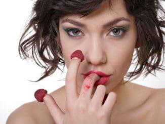 woman eating raspberry