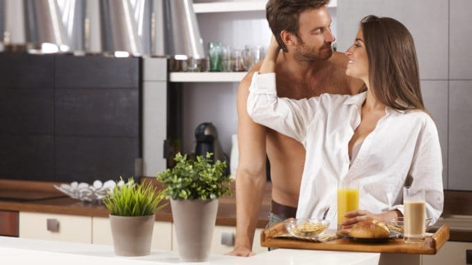 Happy loving couple kissing in the kitchen in the morning.