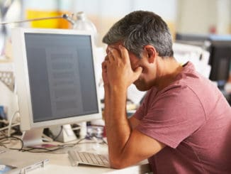 Stressed Man Working At Desk