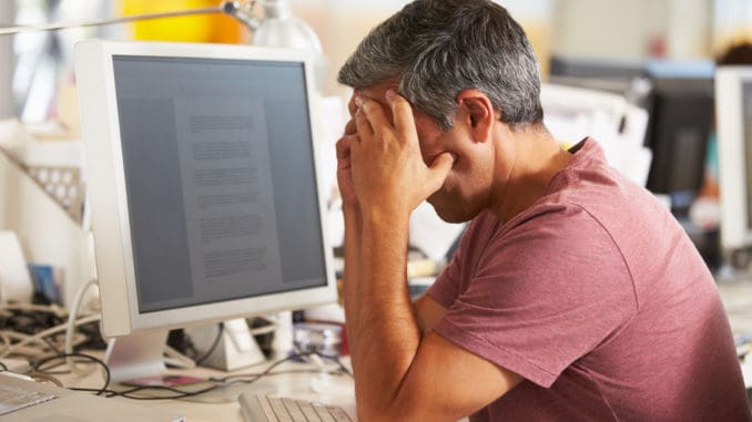 Stressed Man Working At Desk
