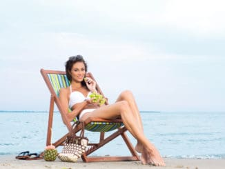 A young and attractive brunette Caucasian woman in a white swimsuit eating fruits and relaxing. The image is taken on a beach background.
