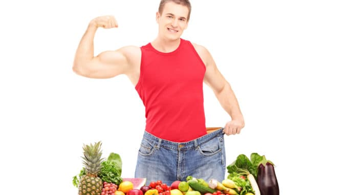 Weight loss man showing his muscles and standing behind a pile of fruits and vegetables, isolated on white background