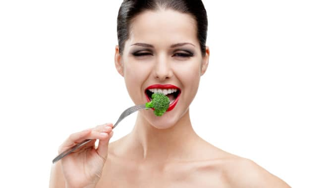 Woman with red lipstick eating broccoli on the stainless fork, isolated on white. Fresh and healthy dieting food