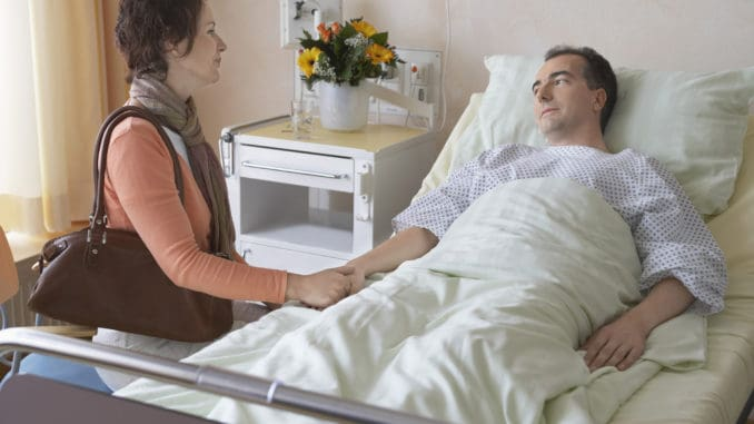 Side view of a women visiting men in hospital