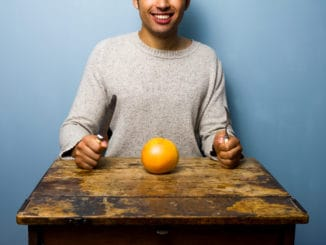 Healthy young man having a grapefruit for dinner at old table