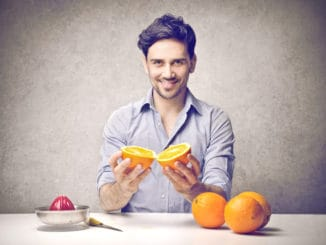Young man holding an orange to do an orange juice