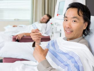 Portrait of male cancer patient eating crushed ice during dialysis at hospital room