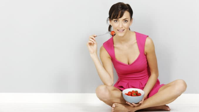 Young woman eating fresh strawberries