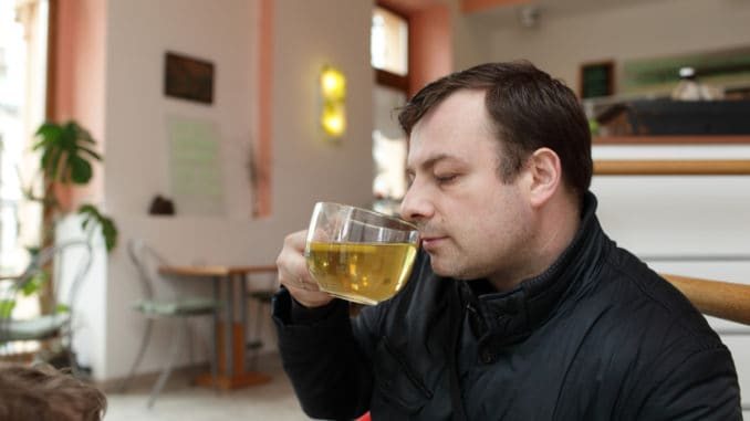 Man drinks green tea in a cafe