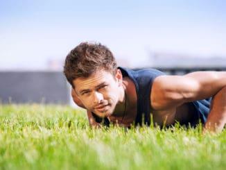 Healthy young man doing pushups outdoors
