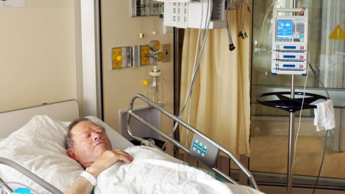 Senior man lying in hospital bed getting oxygen in intensive care unit
