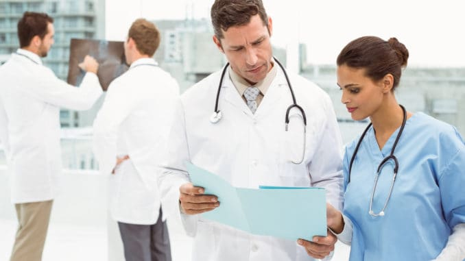 Male doctor and surgeon looking at reports in the medical office