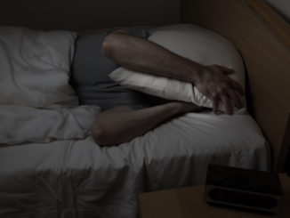 Mature man, with pillow covering entire face, cannot sleep at night from insomnia