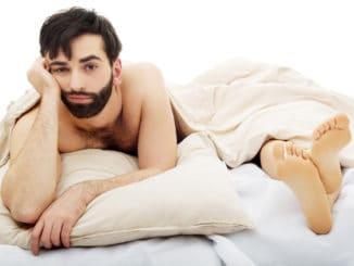 Young handsome depressed men in bed.