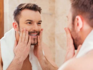 Handsome young man touching his face and smiling while standing in front of the mirror