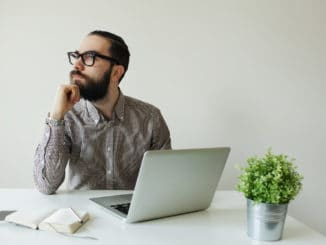 Busy man with beard in glasses thinking over laptop with smartphone on the table