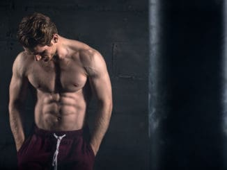 Athletic man with naked torso near concrete wall in the studio looking down