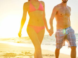 Summer beach couple romantic holding hands at sunset walking in love on honeymoon travel vacation holidays.