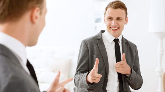 You are winner. Smiling man looking in mirror and pointing on himself with help of his index fingers.