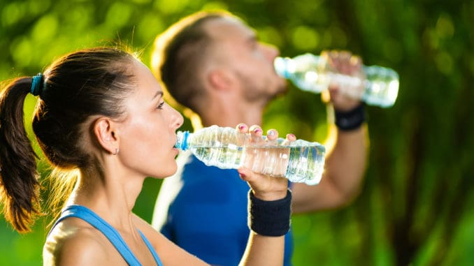 Man and women drinking water from bottle after fitness sport exercise.