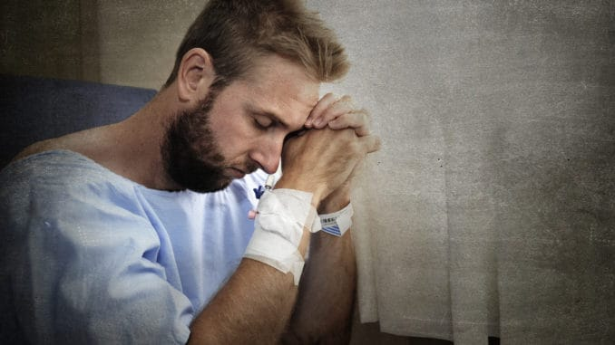 Young injured man in hospital room sitting alone in pain looking negative and worried for his bad health condition sitting on chair suffering depression on a sad lonely background