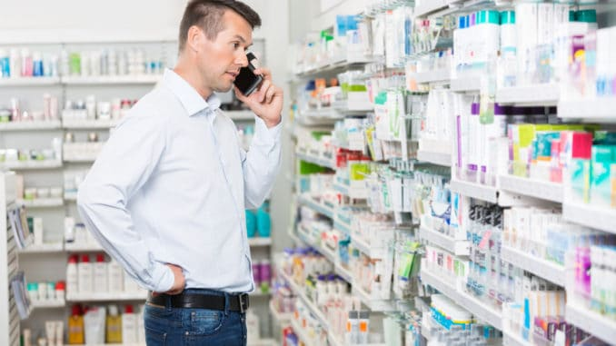 Confused mid adult man using mobile phone while looking at products in pharmacy