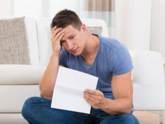 Shocked Young Man Looking At Paper In Living Room