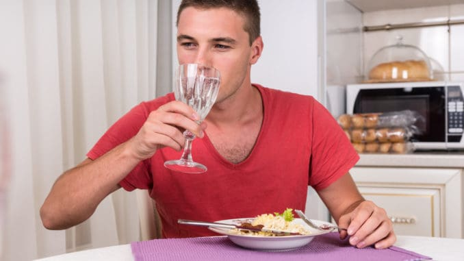Young Man Taking Sip of Water During Dinner of Home Cooked Pasta While Seated at Dining Table in Quaint Kitchen
